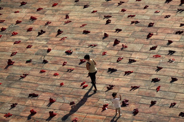 A woman and a child walk amidst an art installation of 745 pairs of female red shoes, put on display by Mexican visual artist Elina Chauvet to protest against gender violence and femicide, at La Constitucion Square in Malaga